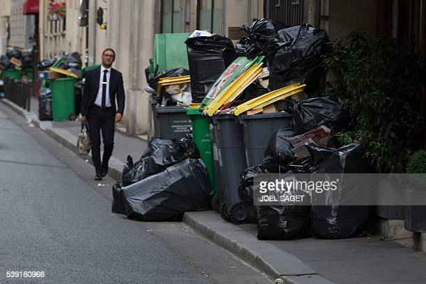 A man walks past a pile of uncollected rubbish on June 10 2016 in Paris Paris Mayor Anne Hidalgo promised on June 10 2016 that 'all rubbish' piling...