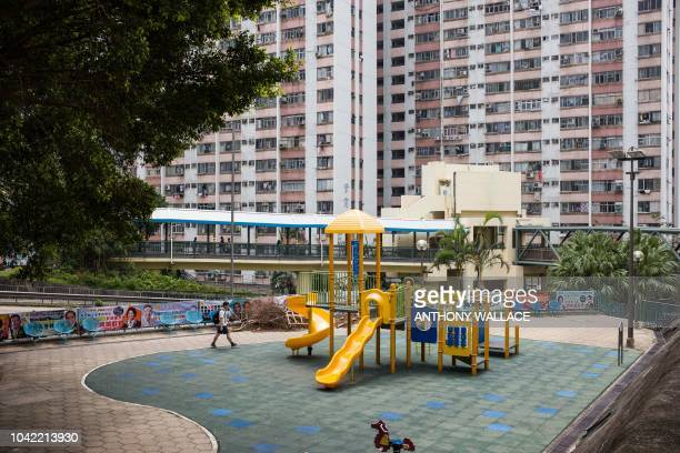 A man walks past a playground near a block of the Choi Wan public housing estate in Hong Kong on September 28 where there were signs of rat...