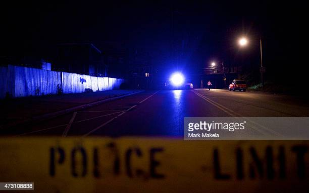A man walks past a police truck with its flickering blue lights near the wreckage of an Amtrak passenger train that derailed carrying more than 200...