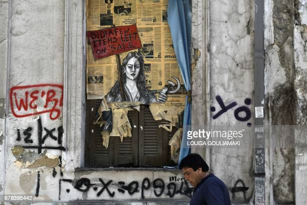 TOPSHOT A man walks past a political graffiti in central Athens by artist Bleeps reading' Bid a few items left on sale' on May 4 2017 one day after...
