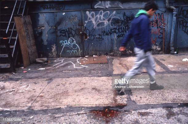 A man walks past a pool of blood on the street in 1990 in New York City during an era of high homicide rates fueled by crack cocaine