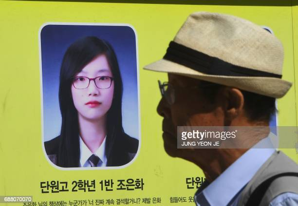 A man walks past a portrait of Cho EunHwa one of four students who went missing in the 2014 South Korea's Sewol ferry disaster near a memorial altar...