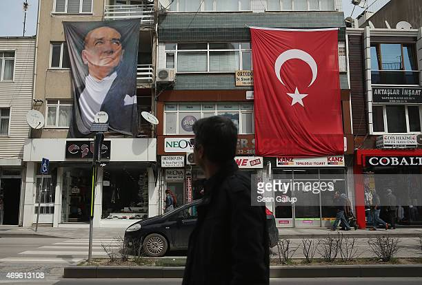 Man walks past a portrait of Mustafa Kemal Ataturk, who served as an Ottoman division commander during the Gallipoli campaign and later founded the...