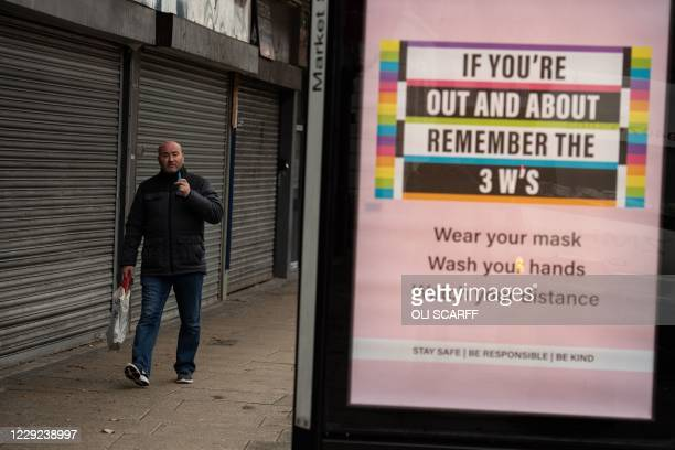 Man walks past a poster advising people of measures to combat the spread of the novel coronavirus, in the high street of Leigh, Greater Manchester,...