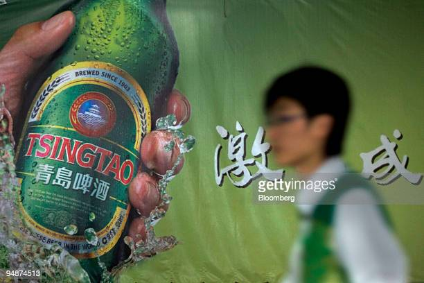 A man walks past a poster at the Tsingtao Brewery Co in Qingdao China on Saturday Oct 11 2008 Tsingtao China's biggest beer company by sales said its...