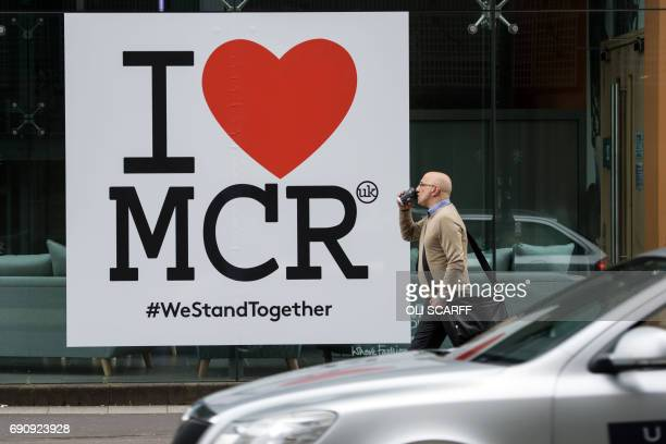 A man walks past a poster displaying a message of defiance to the terror attack of May 22 at the Manchester Arena in Manchester northwest England on...