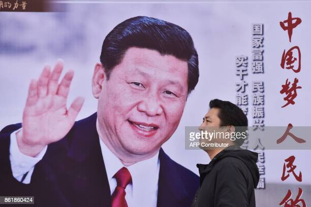 A man walks past a poster featuring Chinese President Xi Jinping with a slogan reading Chinese Dream People's Dream beside a road in Beijing on...