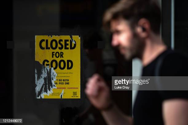 Man walks past a poster from Extinction Rebellion, asking the Government to stop handouts to destructive big businesses as they restart after...