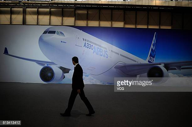 A man walks past a poster of an Airbus A330 aircraft at the Tianjin Airport Economic Area on March 2 2016 in Tianjin China As the first Completion...