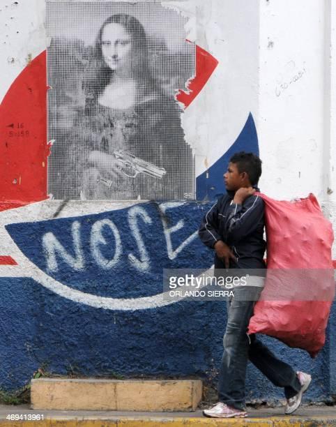 A man walks past a poster of Leonardo da Vinci's 'Mona Lisa' with a gun added to it in the streets of Tegucigalpa on February 14 2014 Honduras a...