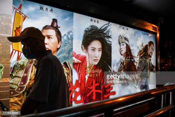 "Man walks past a poster of the Disney movie 'Mulan' at a bus stop in Beijing on September 10, 2020. - Disney's ""Mulan"" remake is facing fresh boycott..."