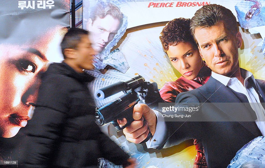 a man walks past a poster of the latest james bond movie die another