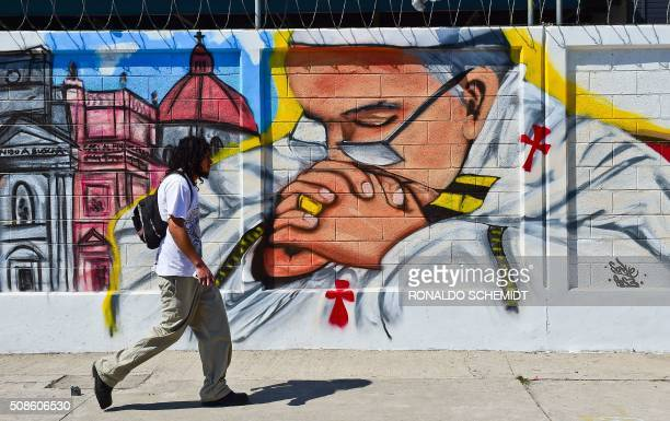 A man walks past a poster welcoming Pope Francis to Ecatepec on the north east side of Mexico City on February 5 2016 The Pope will visit Mexico...