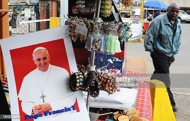 A man walks past a potrait of Pope Francis on sale outside the Holy Basilica in Nairobi on March 24 2013Today marked Palm Sunday in the Catholic...