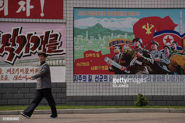 A man walks past a propaganda poster at a silk factory in Pyongyang on May 9 2016 / AFP / Ed Jones