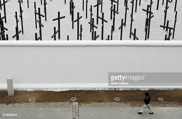 A man walks past a rebuilt section of the Berlin Wall and crosses that commemorate its victims on the day of the memorial's unveiling on October 31...
