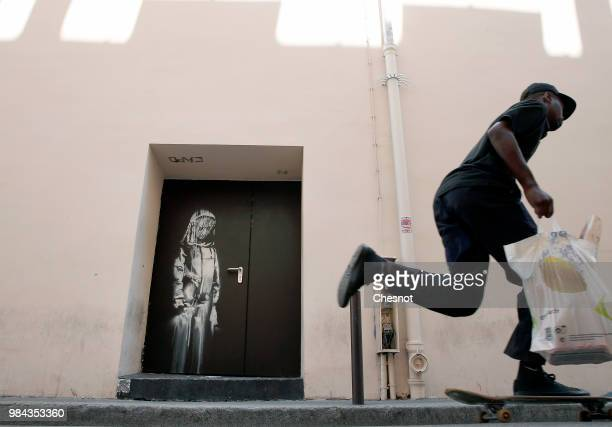 A man walks past a recent artwork attributed to street artist Banksy on June 26 2018 in Paris France Yesterday a new artwork attributed to street...