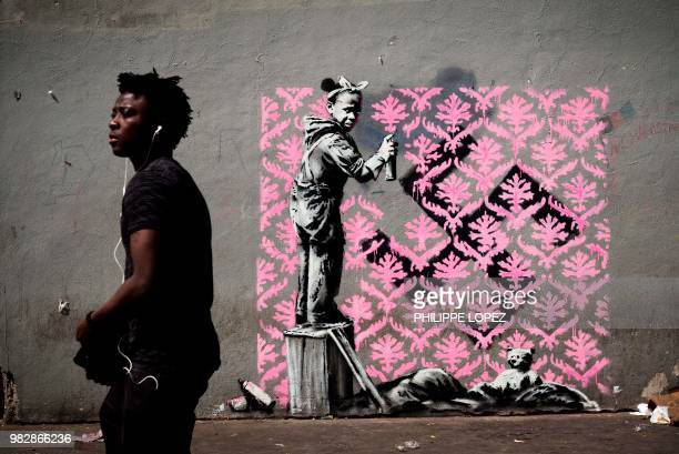 Man walks past a recent artwork by street artist Banksy in Paris on June 24, 2018. - Anonymous street artist Banksy's artwork of a girl painting over...
