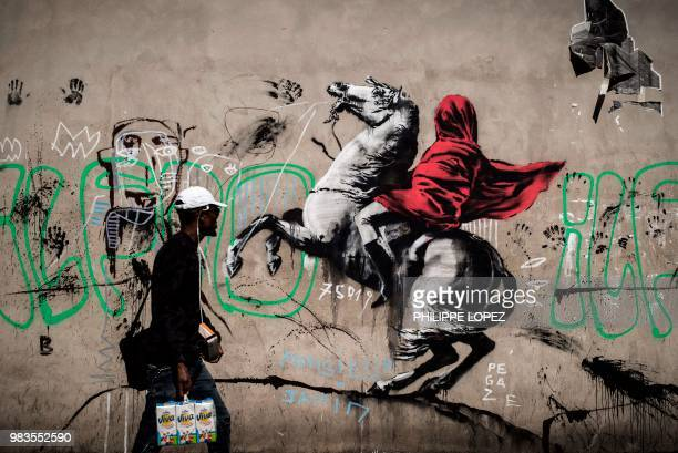 TOPSHOT A man walks past a recent artwork by street artist Banksy in Paris on June 25 2018 Anonymous street artist Banksy's artwork of Napoleon...