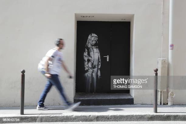 A man walks past a recent artwork by street artist Banksy in Paris on June 25 on a side street to the Bataclan concert hall where a terrorist attack...