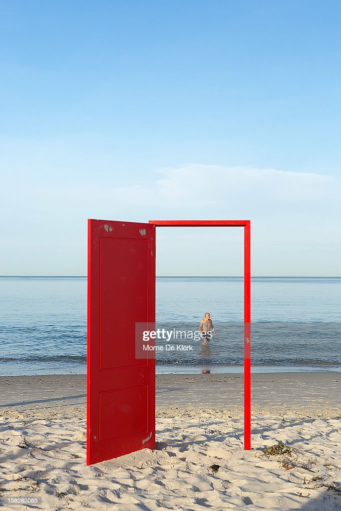 A man walks past a red door to be used in an installation by surrealist artist, Andrew Baines at Henley Beach on December 13, 2012 in Adelaide, Australia. The installation was called 'Doorways To Potential'.