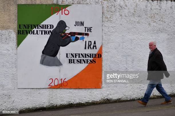 A man walks past a Republican mural in the Bogside area of Derry on March 22 2017 The funeral of Martin McGuinness a onetime Irish Republican Army...