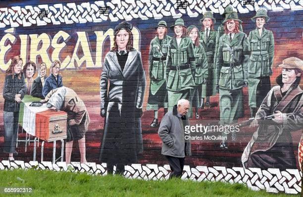 A man walks past a republican mural yards from the home of former Sinn Fein leader Martin McGuinness on March 21 2017 in Londonderry Northern Ireland...