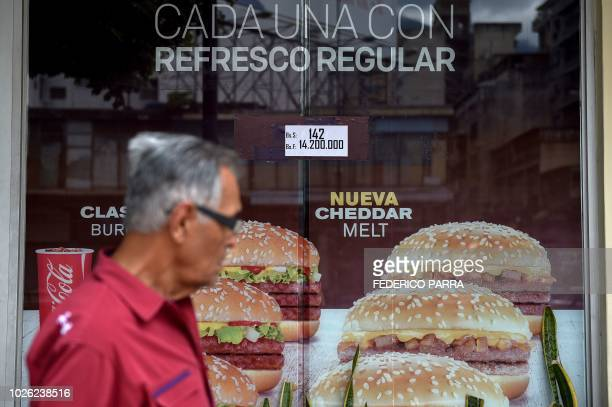 Man walks past a restaurant of US food chain McDonald's displaying the price of hamburgers in bolivars and sovereign bolivars, in Caracas on...