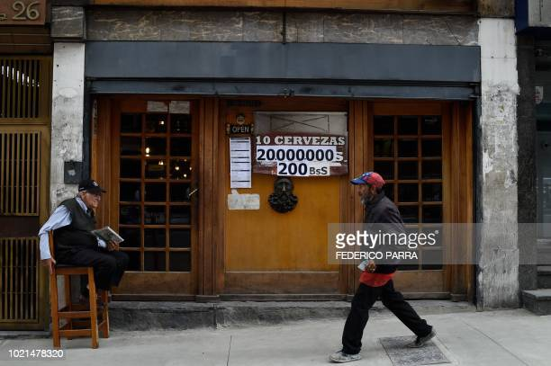 A man walks past a restaurant's sign displaying a price in bolivars and sovereign bolivars in Caracas on August 22 2018 Confusion continues in...