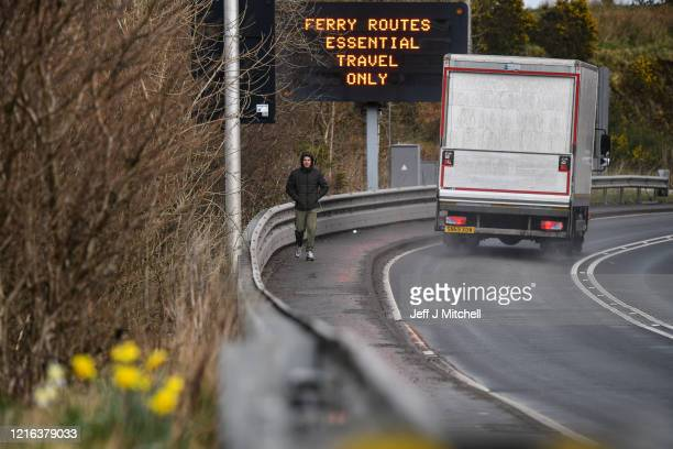 Man walks past a road sign advising of essential ferry travel only in Oban during the Coronavirus crisis on April 2, 2020 in Oban, Scotland. The...