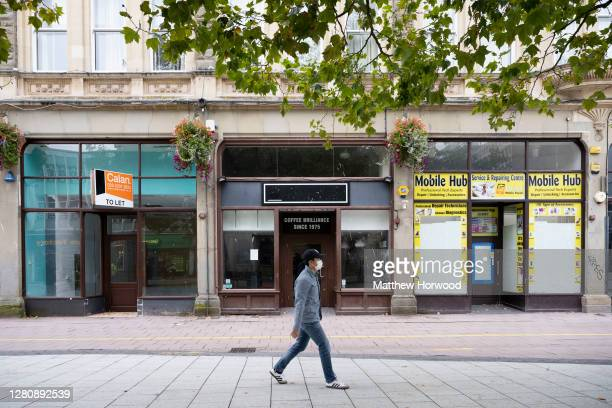 Man walks past a row of shops that have closed down on October 18, 2020 in Cardiff, Wales. The Welsh government is considering a multiweek lockdown...