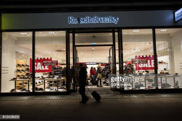 A man walks past a 'sale' advertisement for Russell Bromley on Oxford Street in London