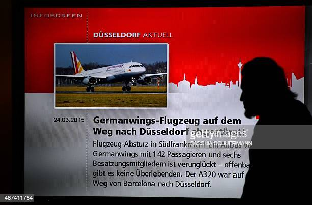 A man walks past a screen displaying news on the crash of a Germanwings plane on March 24 2015 at the airport in Duesseldorf western Germany where...