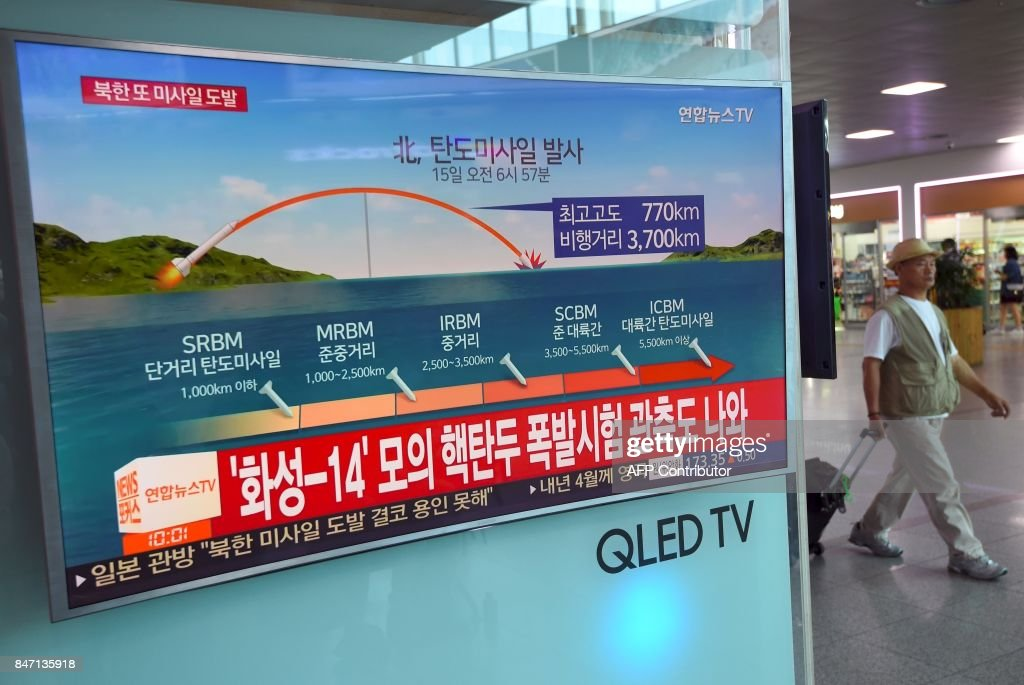 A man walks past a screen showing a news graphic of a North Korean missile launch, at a railway station in Seoul on September 15, 2017. North Korea fired an intermediate range ballistic missile eastwards over Japan and into the Pacific on September 15, the US said, its latest provocation amid high tensions over its banned weapons programmes. / AFP PHOTO / JUNG Yeon-Je