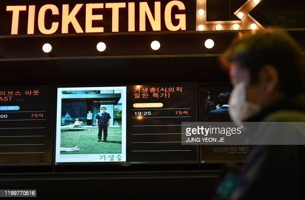 A man walks past a screen showing a poster of Bong Joonho's film 'Parasite' at a cinema in Seoul on February 10 2020 South Korea on February 10...