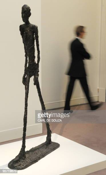 A man walks past a sculpture by Swiss artist Alberto Giacometti entitled 'L'Homme qui marche I' at Sotheby's auction house in London on January 12...