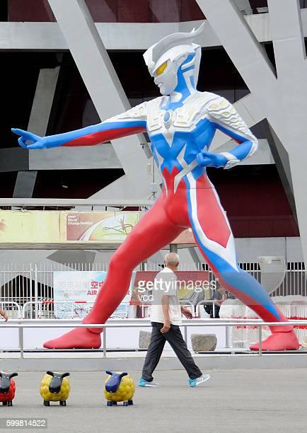 """Man walks past a sculpture of a 5-meter-tall superhero """"Ultraman"""" beside the National Stadium on September 6, 2016 in Beijing, China. The sculpture..."""