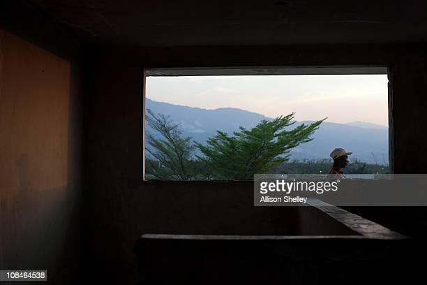 A man walks past a second floor window of a building on the site of the Fort Dimanche prison where many were held in inhumane conditions under the...