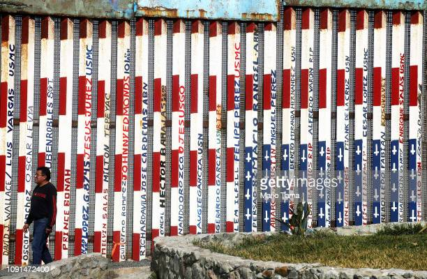 A man walks past a section of the USMexico border barrier painted in American flag colors on January 8 2019 in Tijuana Mexico President Donald Trump...