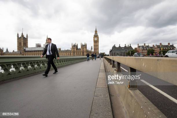 A man walks past a security barrier which sits between the road and pavement of Westminster Bridge on June 5 2017 in London England Seven people were...