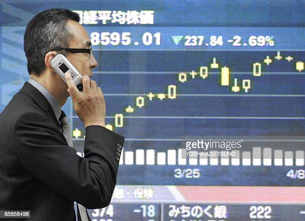 A man walks past a share prices board in Tokyo on April 8 2009 Japanese share prices closed off 269 percent on April 8 dragged down by heavy losses...
