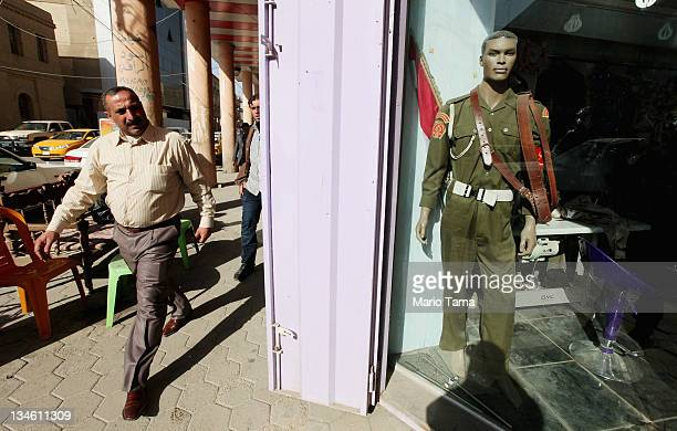 A man walks past a shop that sells uniforms to members of Iraq's military and police forces on December 3 2011 in Baghdad Iraq Members of the Iraqi...