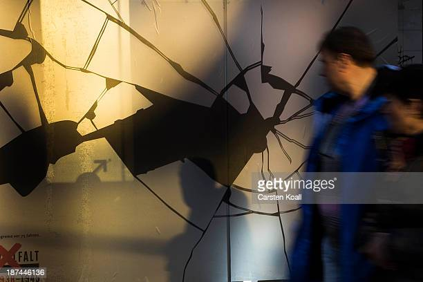 A man walks past a shop window made to look like it has been smashed to commemorate the 75th anniversary of the Kristallnacht pogroms on November 9...