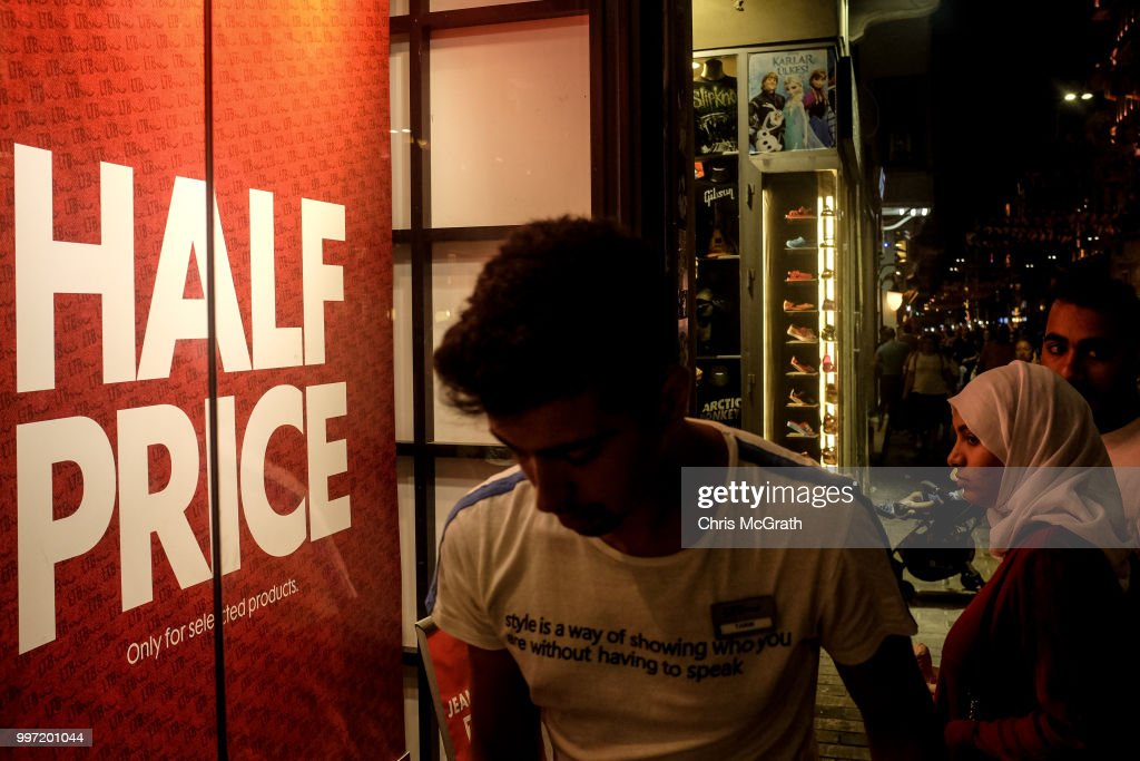 A man walks past a shop window promoting a sale on Istanbul's famous Istiklal street on July 12, 2018 in Istanbul Turkey. Following Turkey's President Recep Tayyip Erdogan's re-election victory and the appointment of his son-in-law Berat Albayrak to lead the Treasury and Finance Ministry fears are growing that Turkey's economy is heading into crisis . The Turkish Lira, has plunged by approximately one-fifth this year raising prices for businesses and households.