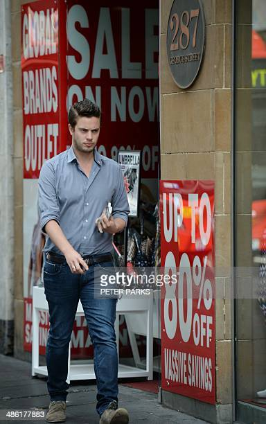 A man walks past a shop with sale signs on a retail street of Sydney on April 23 2014 Australian inflation eased in the first quarter of the year...