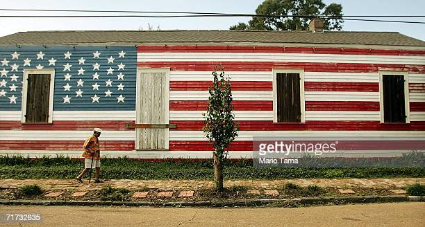 A man walks past a shotgun house painted with the American flag in the 9th Ward August 28 2006 in New Orleans Louisiana The first anniversary of...