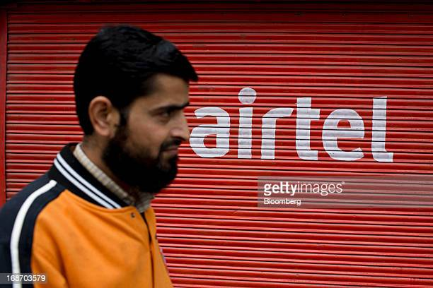 A man walks past a shutter of a closed store displaying the Bharti Airtel Ltd logo in Srinagar India on Sunday May 12 2013 Indian inflation eased to...