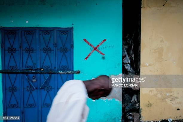 A man walks past a shuttered shop in the capital Moroni on Grande Comore island on February 22 2015 which has been marked with a red cross allegedly...