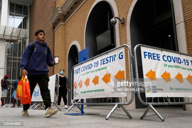 """Man walks past a sign advising members of the public of a """"Free Covid-19 Testing"""" site in south London, on July 31, 2021. - Coronavirus case numbers..."""