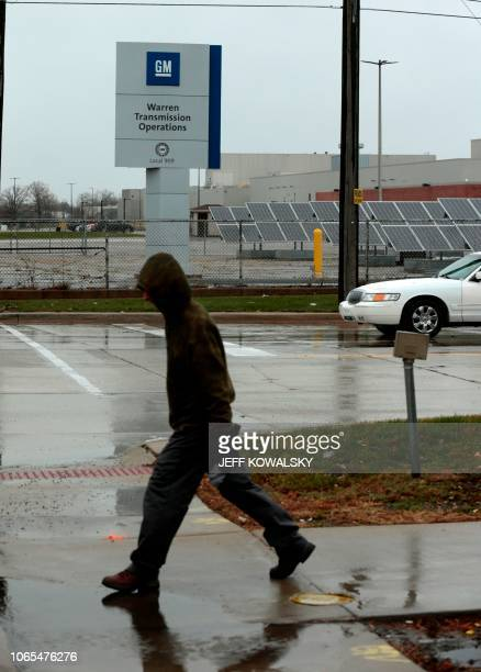 A man walks past a sign at General Motors as they announced the closing of multiple facilities including the Warren Transmission Operations on...